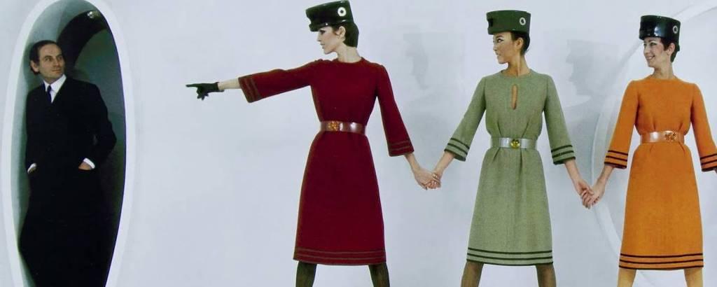 Três mulheres vestem vestido coloridos. Uma veste vermelho, a outra verde e a outra laranja. A mulher da esquerda aponta para homem ao fundo