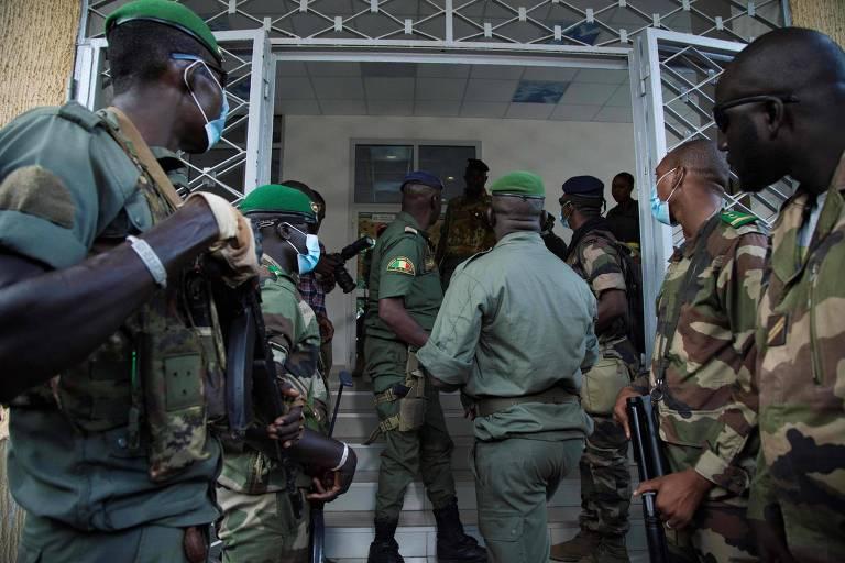 Soldados que participaram do golpe contra o governo civil aguardam em frente ao Ministério da Defesa enquanto integrantes da junta militar e representantes da oposição se reúnem dentro do prédio
