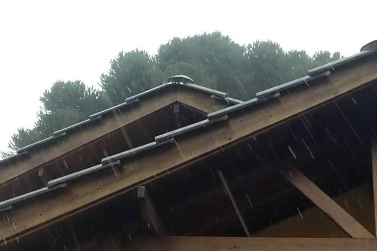 Flocos de neve e chuva congelada em São Francisco de Paula, nos Campos de Cima da Serra, no Rio Grande do Sul, na tarde desta quinta-feira (20); na foto vemos uma espécie de chuva fina e bastante visível caindo sobre telhados de madeira
