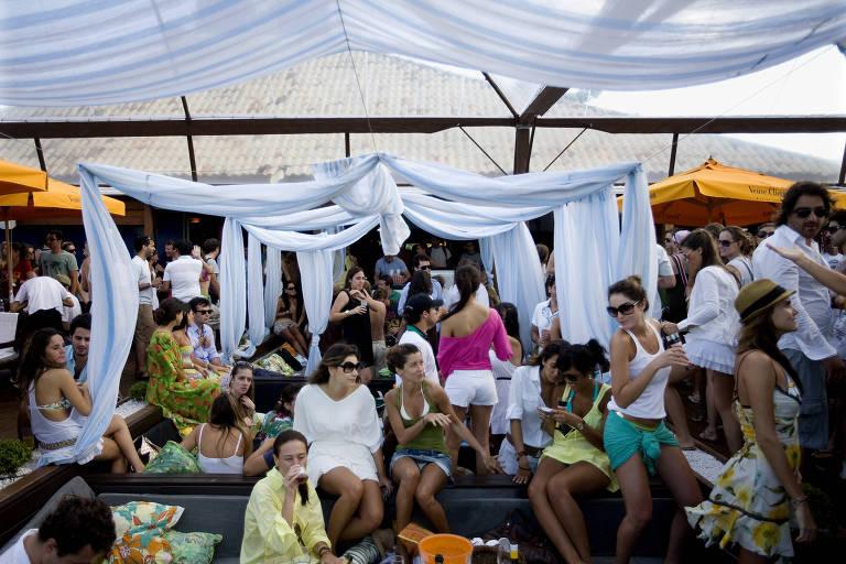Café de la Musique, na praia de Jurerê Internacional, em Florianópolis; vemos estruturas de metal e vidro, com drapeados brancos formando dosséis; há muitas pessoas com roupa de verão dançando e conversando no ambiente