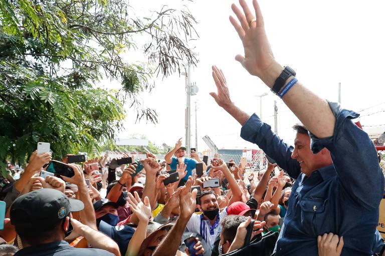 bolsonaro de braços para o alto em meio a aglomeração de pessoas
