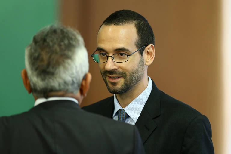 Arthur Weintraub, assessor especial da Presidência, de terno, no centro da foto. Em primeiro plano há um homem grisalho de costas