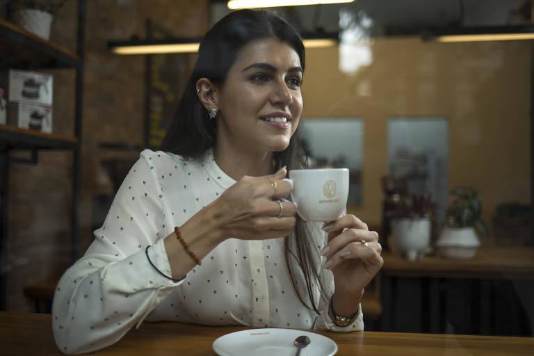 Mulher com blusa branca segura xícara de café e olha para o lado