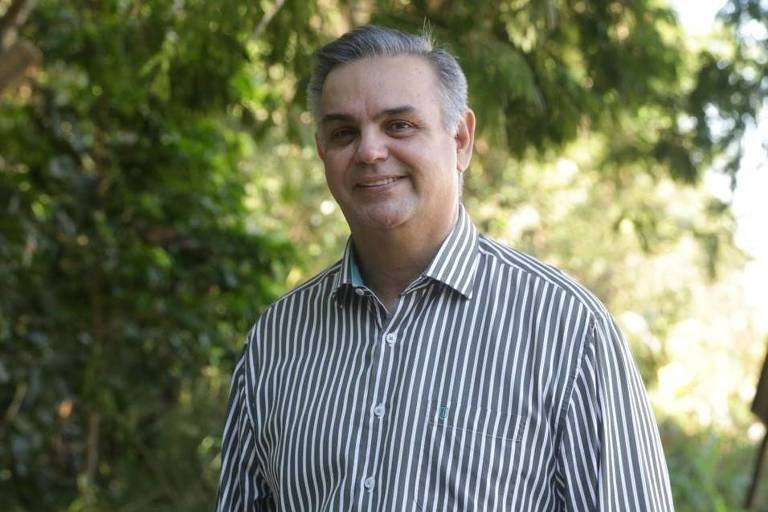 Vasques, um homem de cabelos brancos que veste uma camisa listrada, numa área verde
