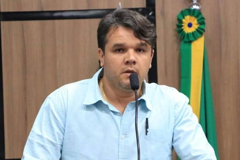 Joubert falando ao microfone. Atrás deles, uma bandeira com faixas nas cores verde e amarela