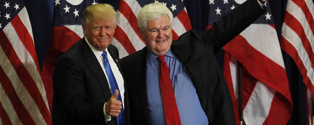 Newt Gingrich, com o braço esquerdo levantado, está ao lado de Donald Trump, que acena com um sinal de joia