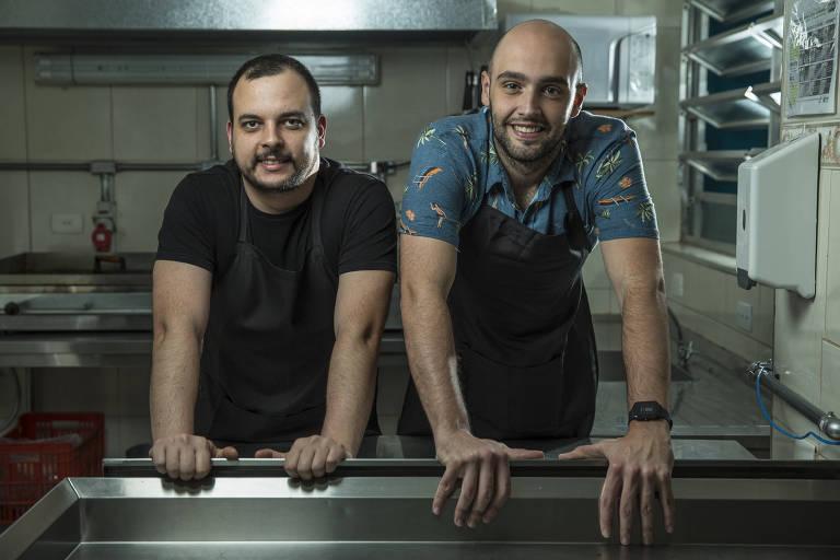 Dois homens em pé, apoiados em balcão de metal, sorrindo, em cozinha