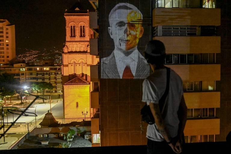 Homem observa projeção em protesto ao ex-presidente colombiano Álvaro Uribe em prédio de Medelín