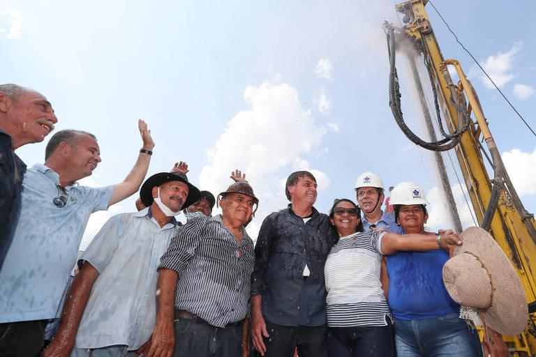 Presidente da República Jair Bolsonaro, acompanhado de moradores da comunidade, se molham nas águas do poço artesiano