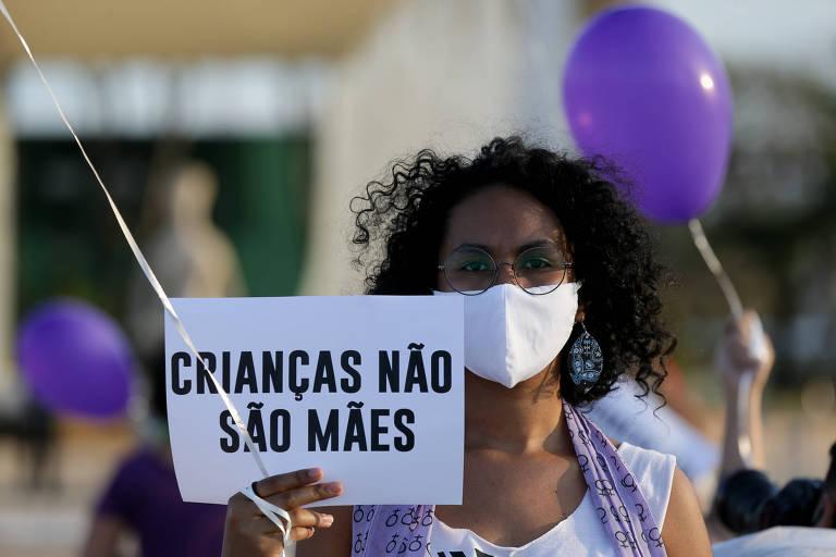 """Mulher parda de máscara segura cartaz em que se lê """"crianças não são mães""""; por trás, se vê dois balões roxos"""