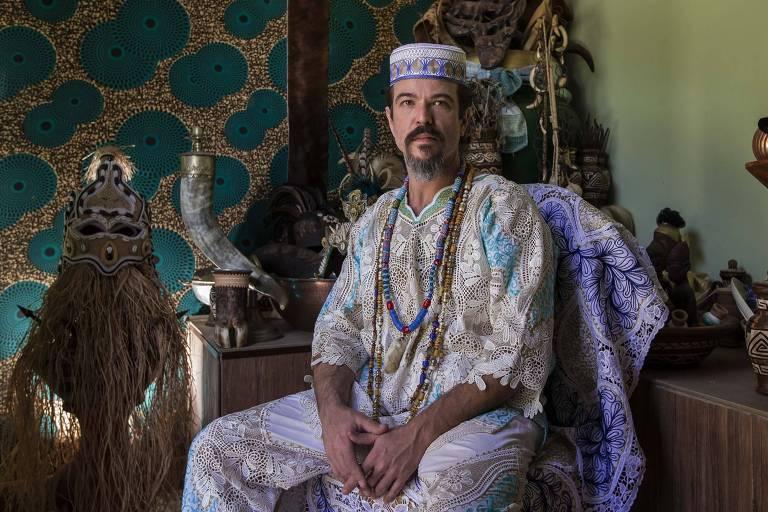O babalorixá com os trajes religiosos sentando em um banco