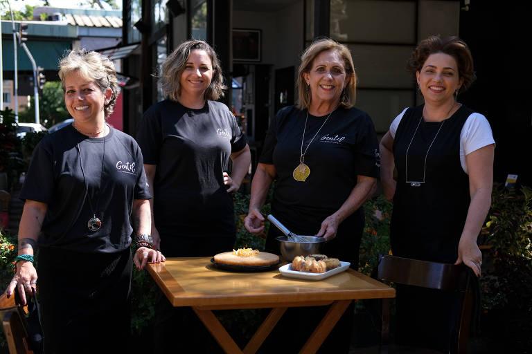As três irmãs, sócias, com a mãe. As quatro estão em pé atrás de uma mesa com petiscos