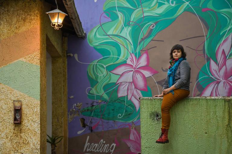 Mulher jovem sentada em mureta de perfil com grafite colorido ao fundo