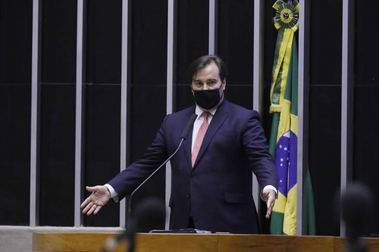 Maia de braços abertos, com a bandeira do Brasil atrás