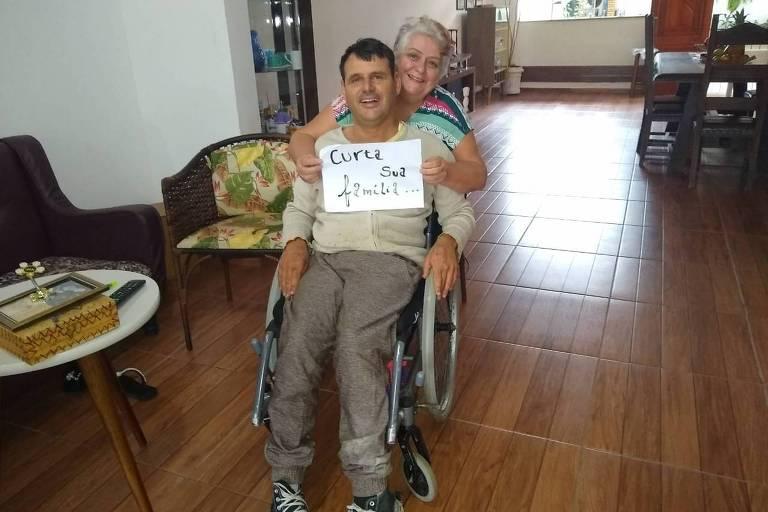 """Tarcísio Duarte, de 37 anos, na cadeira de rodas, sorrindo e acompanhado da mãe Marli, que segura um cartaz com a frase """"Curta sua família"""""""