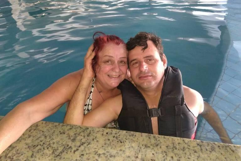 Tarcísio Duarte, 37, com a mãe, Marli, sorrindo na beirada de uma piscina