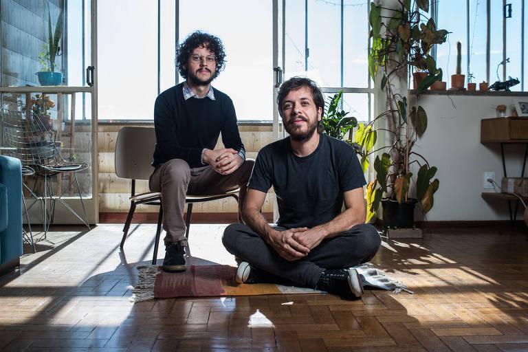 Vinícius de Souza e Filipe Lampejo na sala do apartamento em que Vinícius vive. Vinícius está sentado à esquerda, em uma cadeira, e Filipe, à sua direita, está sentado no chão, com as pernas cruzadas. Atrás do casal, há uma grande janela e algumas plantas. Ambos vestem preto.