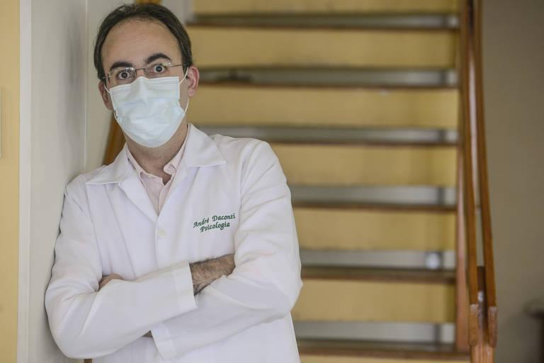 O psicólogo está à frente de uma escada, encostado na parede, usando máscara e óculos de grau, de braços cruzados.