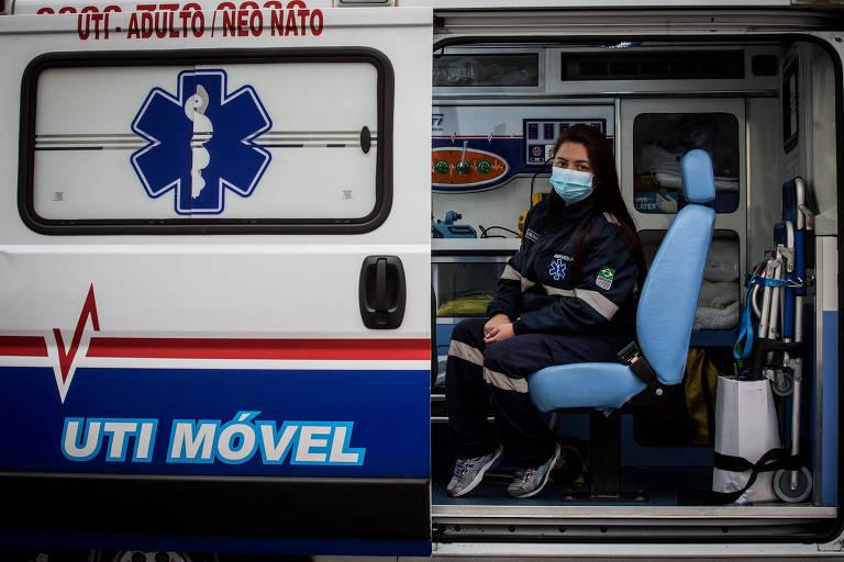 """A enfermeira Giuliana Valderano está sentada na poltrona dentro de uma UTI móvel (ambulância), onde trabalha. O carro é azul e branco e está marcado """"UTI móvel"""" na lataria. Giuliana está vestida com um macacão azul, de tênis e uma máscara azul claro."""