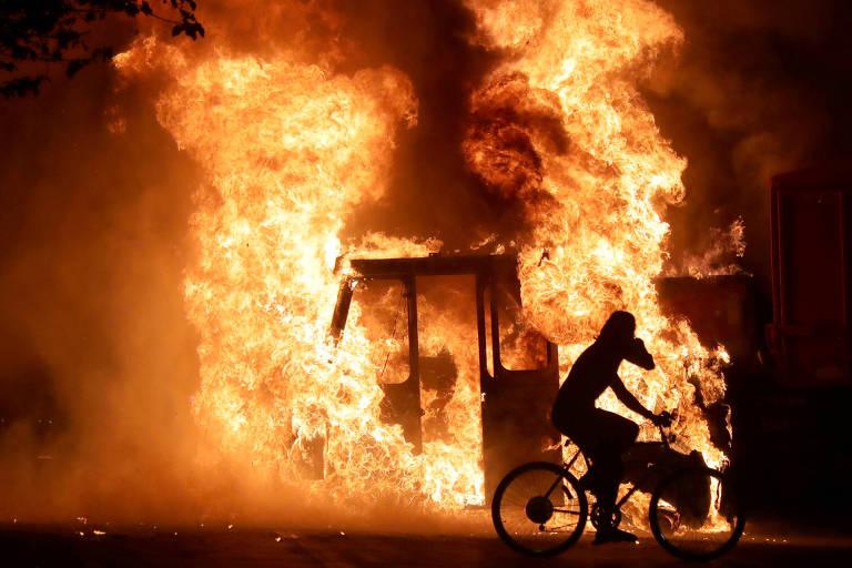 Cicilista passa em frente a caminhão incendiado próximo ao tribunal de Kenosha, durante protesto contra a morte de Jacb Blake