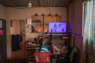 Delia Huamani, 10, watches a broadcasting of remote school lessons at her home in Pedregal, Peru, Aug. 13, 2020. (Marco Garro/The New York Times)