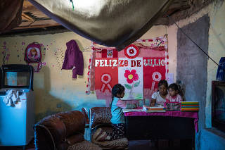 Gabriela Rojas, center, helps her sister Luna, right, and neighbor Yoiz Vasquez, left, with their remote schoolwork at her home in Lima, Peru, Aug. 13, 2020. (Marco Garro/The New York Times)