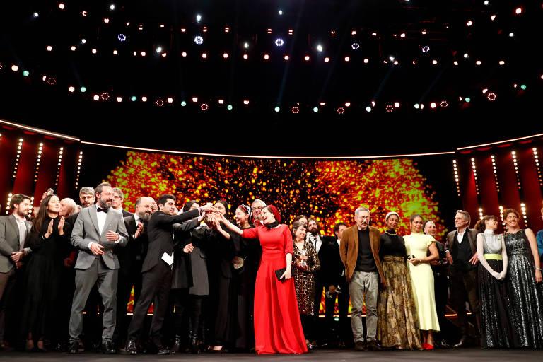Pessoas usam roupas de gala em palco