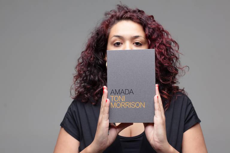 A dramaturga está segurando um livro de capa cinza em frente ao seu rosto, onde só seus olhos estão visíveis. Veste uma camiseta preta.