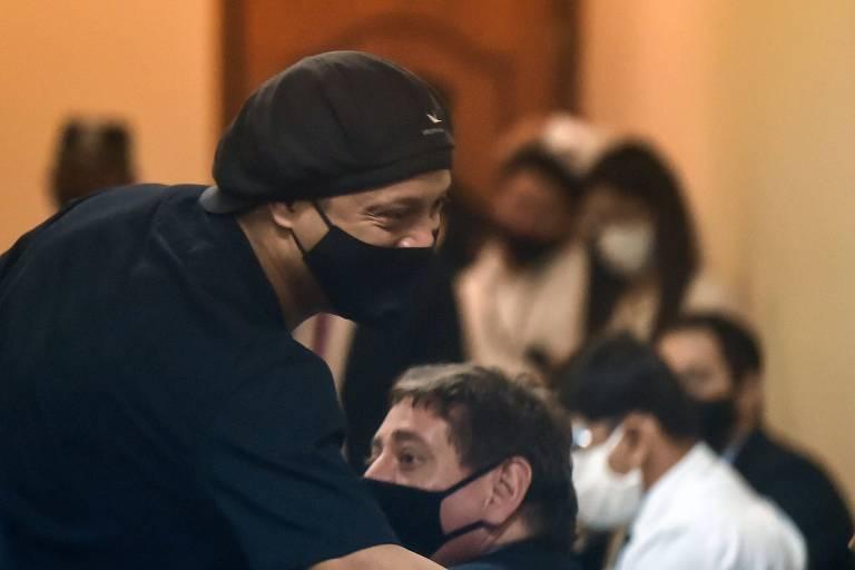 Ronaldinho, de máscara, cumprimenta pessoas na audiência