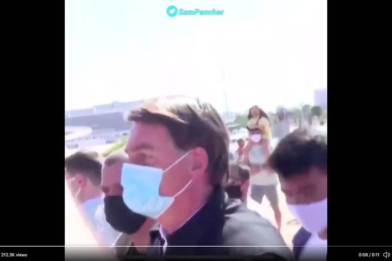 Frame do vídeo que mostra Bolsonaro atacando repórter; o presidente aparece de máscara em meio a pessoas
