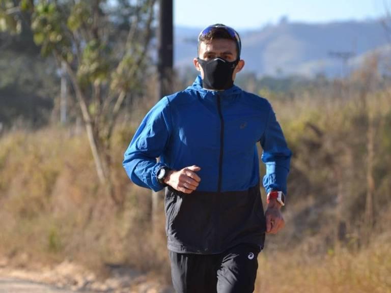 O corredor Ederson Vilela, em primeiro plano, trajando máscara preta e casaco azul corre na zona rural de Caçapava (SP)