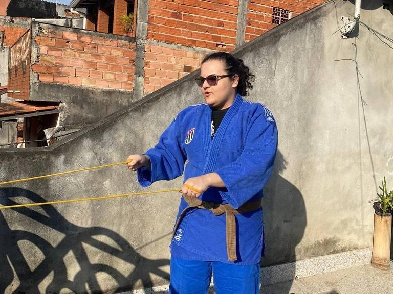 A judoca Rebeca Silva, em primeiro plano e vestindo kimono azul, realiza treino físico em sua casa durante a quarentena, na cidade de São Bernardo (SP)