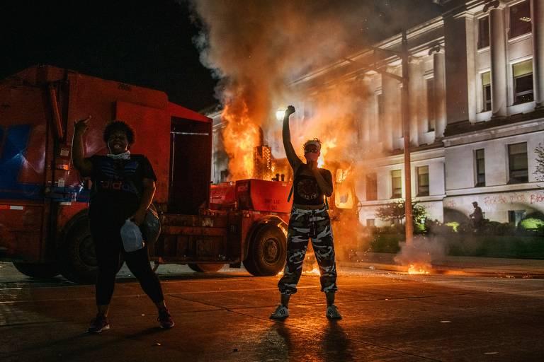 Manifestante faz gesto do movimento antirracista em frente a caminhão incendiado em Kenosha, na noite de segunda (24)