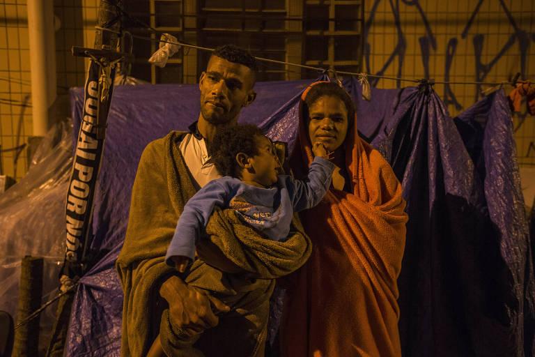 Daiane, 27, Maicon Dias, 35, e Maicon Dias, 10 meses, moram em uma barraca, no Belenzinho, em São Paulo. Na foto, eles se cobrem com cobertores para aguentar o frio fora da barraca