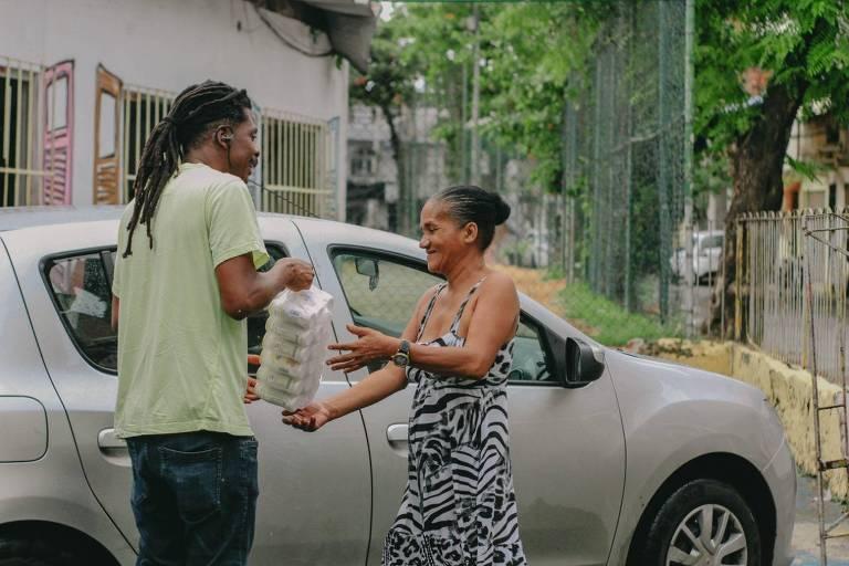Joselito Crispim entrega um pacote de mantimentos para uma mulher idosa. Ambos estão de pé, de lado, em frente a um carro estacionado na comunidade bahiana.