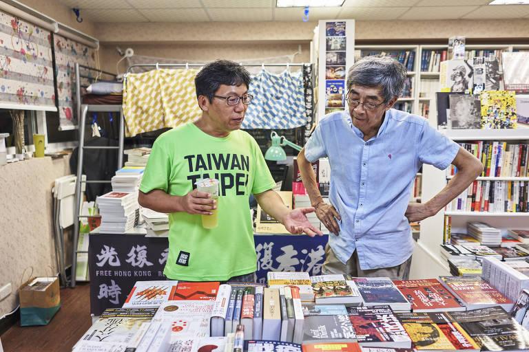 Dois homens chineses conversam em frente a centenas de livros