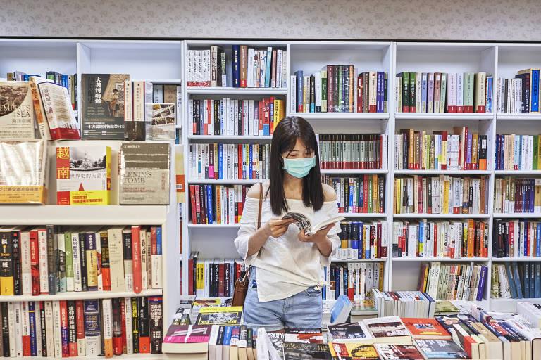 Chinesa com máscara de proteção a coronavírus folheia livro ao lado de estante da biblioteca