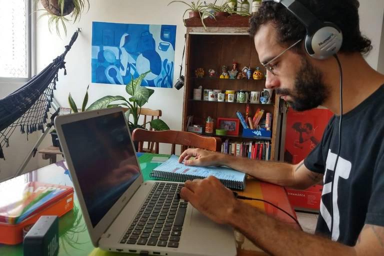 No lado direito da foto, homem está sentado em frente a um computador. Ele usa fones de ouvido e camiseta preta. Do lado esquerdo, há uma rede, uma janela e um quadro. No centro, há uma prateleira com canecas e plantas. Ele encena um espetáculo remotamente.
