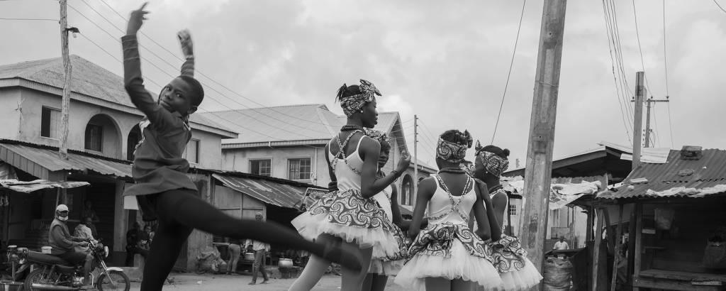 Crianças dançam em rua com casas pobres