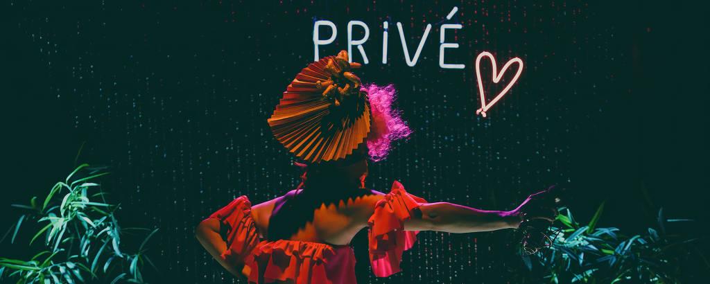 drag faz performance em palco redondo iluminado por luzes neon
