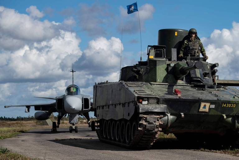 Blindado e caça Gripen manobram em rodovia de ilha sueca durante alerta militar