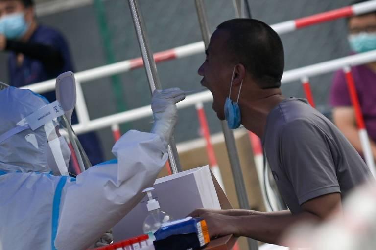 Homem faz teste para detectar o novo coronavírus, uma das medidas adotadas na China