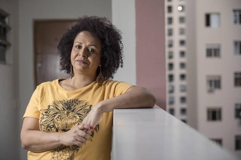 A assistente social Luciana Reis Oliviera, 48, em seu apartamento no centro de São Paulo; Luciana tem um meio sorriso na foto, em que aparece usando uma camiseta amarela, apoiada no parapeito do corredor do prédio, que é aberto