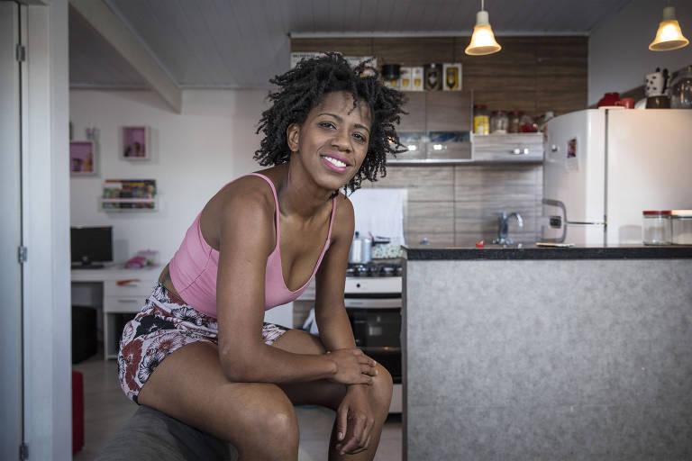 A pedagoga Ana Paula Evangelista Neris, 34, em sua casa no Itaim Paulista, zona leste de São Paulo; Ana Paula é negra, tem os cabelos crespos curtos e sorri na foto, sentada no encosto do seu sofá cinza, tendo ao fundo a cozinha de sua casa, que é aberta para casa; ela usa uma regata justa rosa e um short estampado