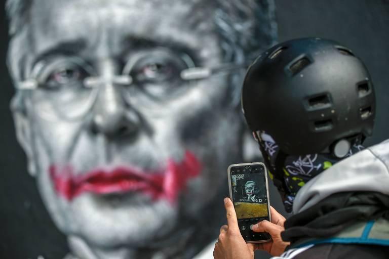 Em Bogotá, homem tira foto de imagem em mural do ex-presidente da Colômbia Álvaro Uribe
