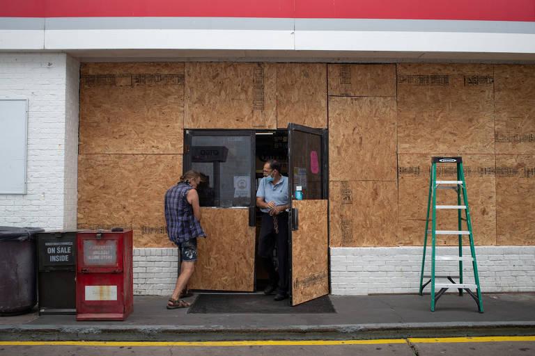 Homem coloca tapumes em loja de conveniência na cidade de Galveston, no Texas, antes da chegada do furacão Laura