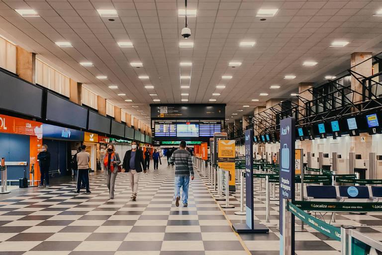 Pessoas andando em saguão de aeroporto, com o piso quadriculado em preto e branco