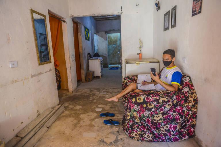 Adolescente sentado no sofá da sala segurando um celular em uma das mãos e um caderno escolar em outra