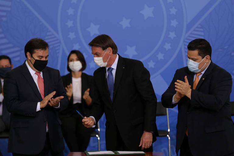 O presidente Jair Bolsonaro, no centro, dá caneta ao presidente da Câmara, Rodrigo Maia, que está do lado direito. No lado esquerdo, o presidente do Senado, Davi Alcolumbre, aplaude. Todos estão de máscara.