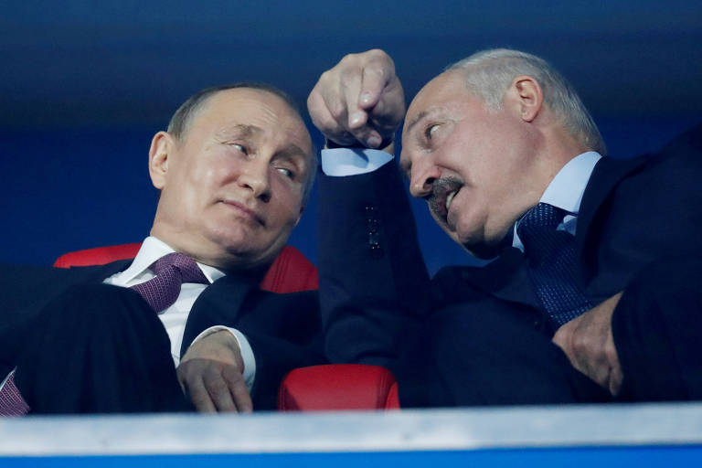 Sentados em cadeiras de um estádio de futebol, Putin e Lukachenko conversam, olhando um para o outro.